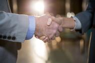 Close-up of businessman shaking hands with colleague in the office.jpeg