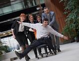 business people group at modern office indoors have fun and push office chair on corridor.jpeg