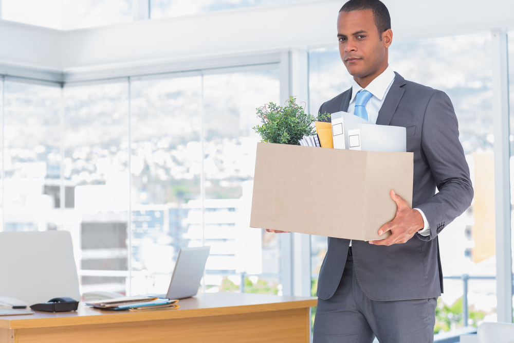 Sad businessman leaving his company while he is holding a box-1
